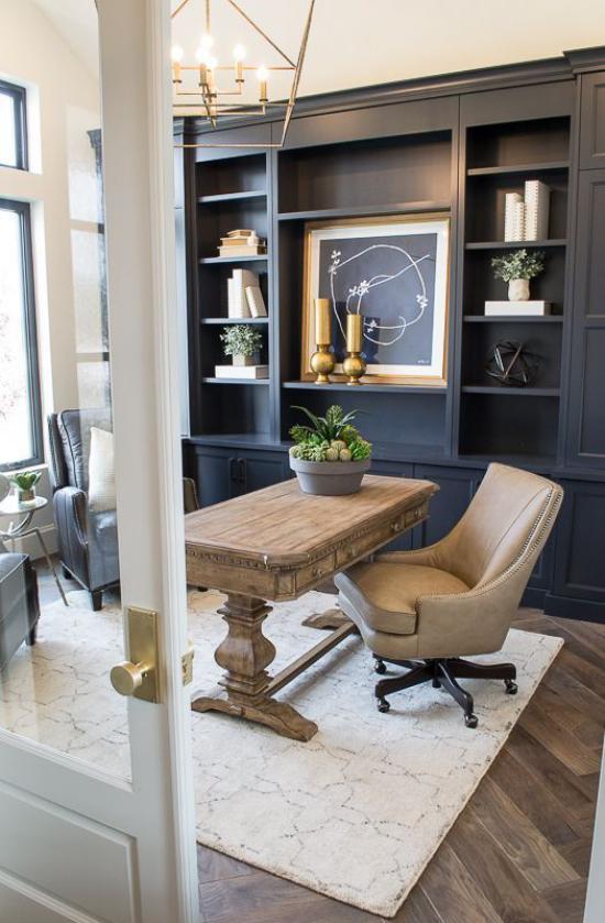 Home Office im Landhausstil Schreibtisch aus echtem Holz in der Mitte des Raums heller Teppich dunkler Wandschrank