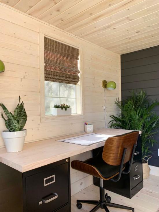 Home Office im Landhausstil immergrüne Zimmerpflanzen erfrischen das Ambiente großer Schreibtisch Stuhl Fensterrollo