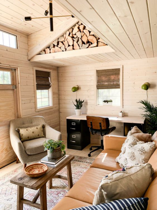 Home Office im Landhausstil schön eingerichtetes Arbeitszimmer bequemes Ledersofa weiche Kissen Holz an der Decke
