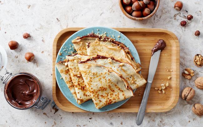 Pfannkuchen leicht gemacht gefaltet auf dem Teller serviert mit Nutella und Nüssen