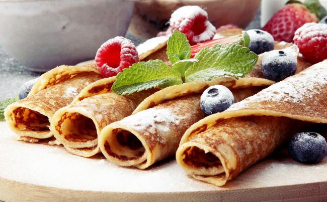 Pfannkuchen leicht gemacht gerollt mit Puderzucker Beeren Minze Blätter darauf