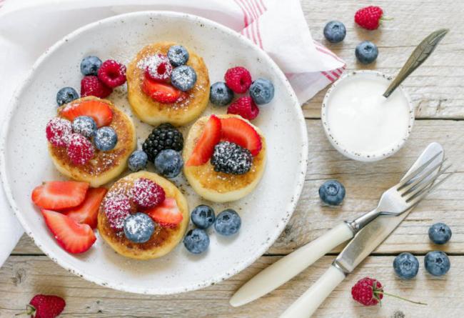 Pfannkuchen leicht gemacht kleine runde teigwunder mit frischen Beeren und Puderzucker