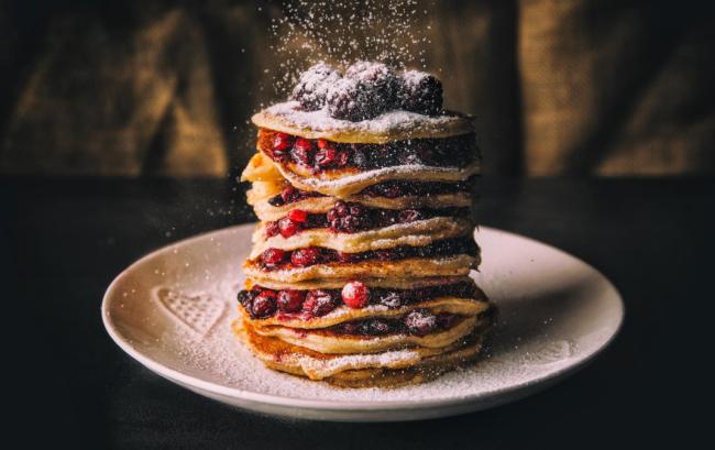 Pfannkuchen leicht gemacht leckere Palatschinken auf einem Teller gestapelt mit frischen Beeren und Puderzucker
