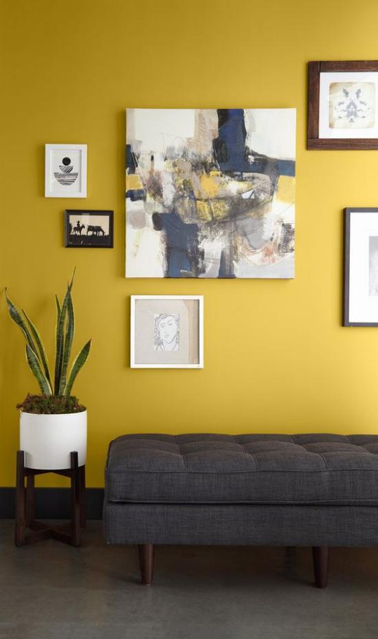 Trendfarben 2021 im Interieur Wohnzimmer graue Liege gelbe Akzentwand Gemälde ein guter visueller Ausgleich