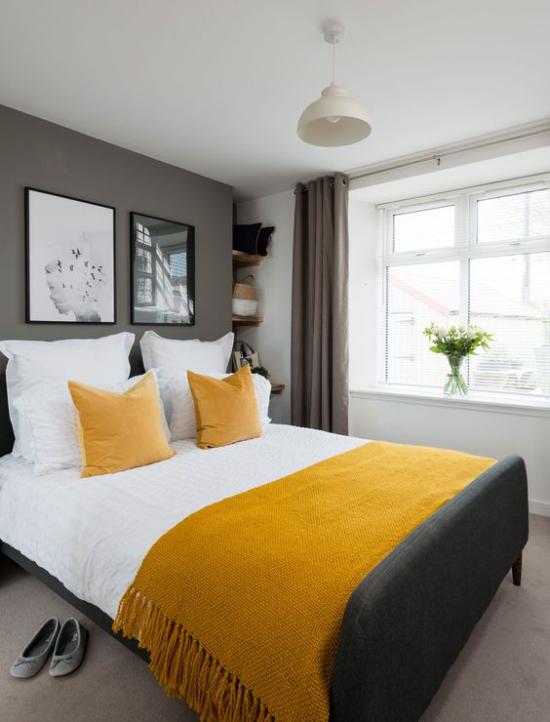 Trendfarben 2021 im Interieur gemütliches Schlafzimmer viel Wärme ausstrahlen gelbe Decke Kissen graue Akzentwand ideen
