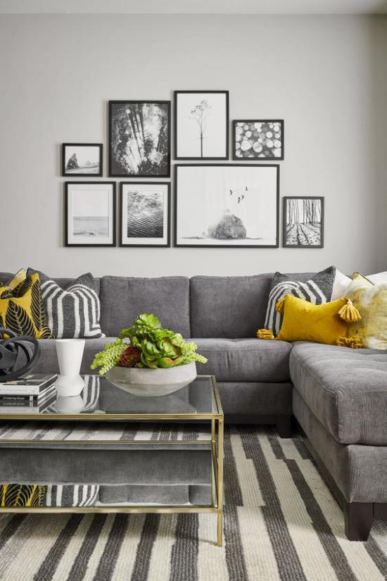 Trendfarben 2021 im Interieur gemütliches Wohnzimmer Wandbilder graues Sofa kleine gelbe Akzente erfrischen das Ambiente