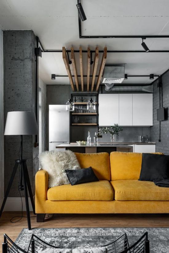 Trendfarben 2021 im Interieur graue Wohnküche Industrial Style gelbes Sofa Blickfang
