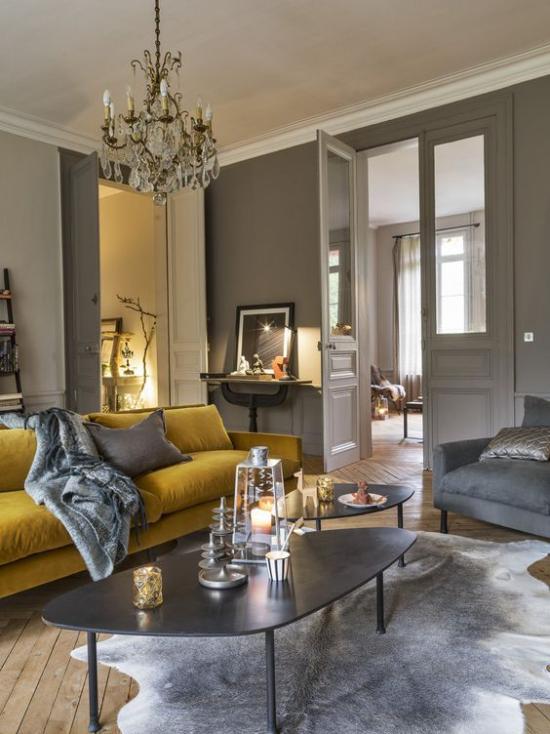 Trendfarben 2021 im Interieur graues Wohnzimmer ein Blickfang gelbes Sofa