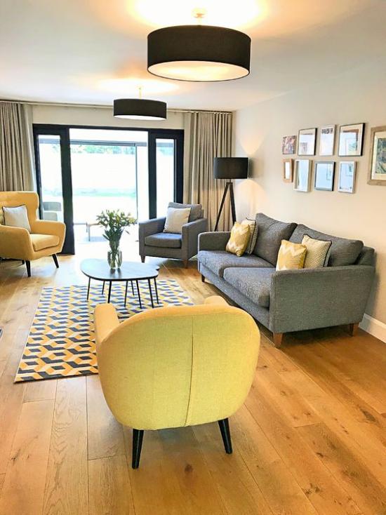 Trendfarben 2021 im Interieur schickes geräumiges Wohnzimmer graue Couch ein grauer Sessel zwei gelbe Sessel sehr einladend