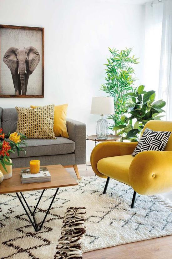 Trendfarben 2021im Interieur Wohnzimmer graues Sofa gelber Sessel Teppich immergrüne Zimmerpflanzen viel Sonnenlicht