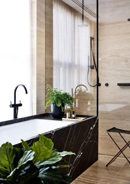 Badezimmer Trends 2021 Badewanne außen schwarzer Marmor Fenster exotische Grünpflanze auffälliger Look