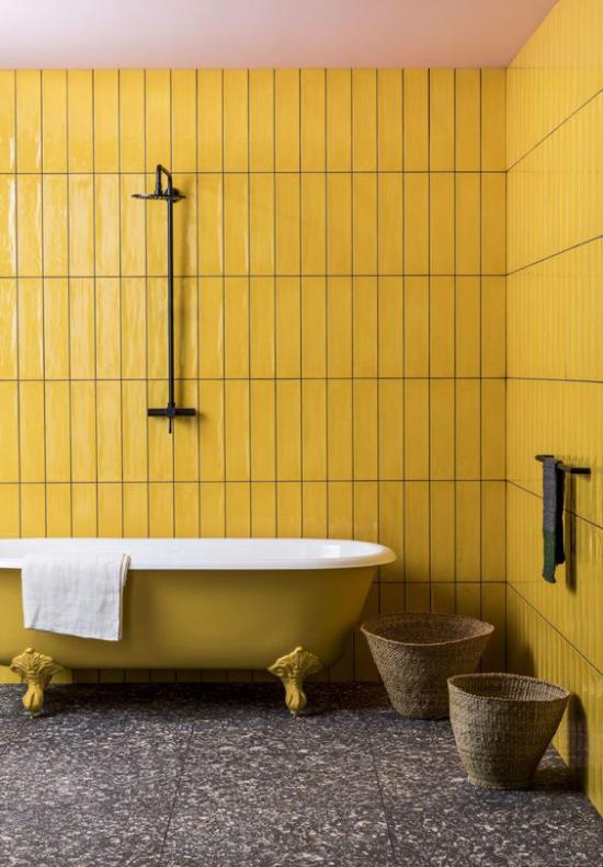 Badezimmer Trends 2021 Retro Design gelbe Wandpaneele gelbe Badewanne mit Löwenfüßen dunkler Terrazzoboden