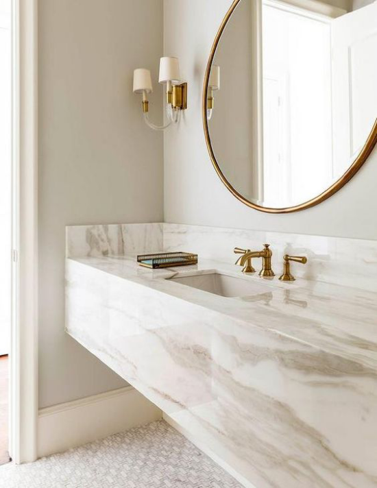 Badezimmer Trends 2021 elegantes Baddesign weißer Marmor Waschtisch großer runder Spiegel Wandlampen