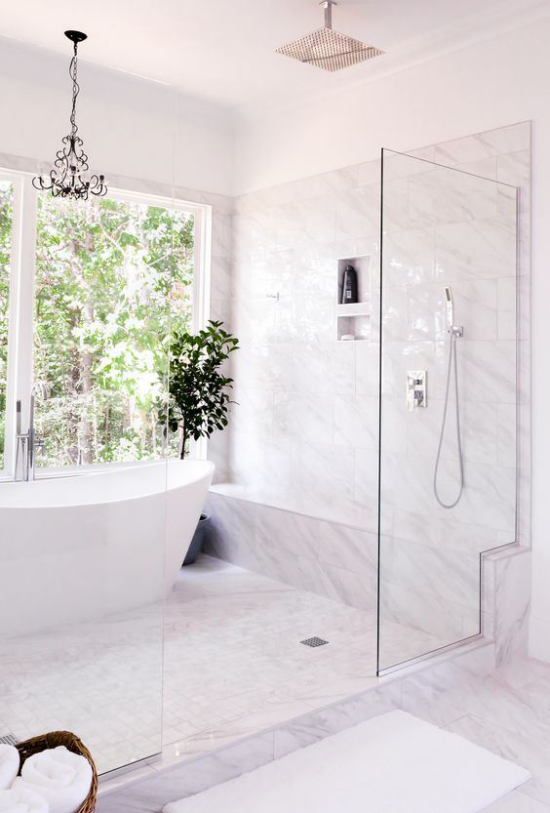 Badezimmer Trends 2021 großes Fenster zum Hinterhof weiße Badewanne helle Fliesen Glastür