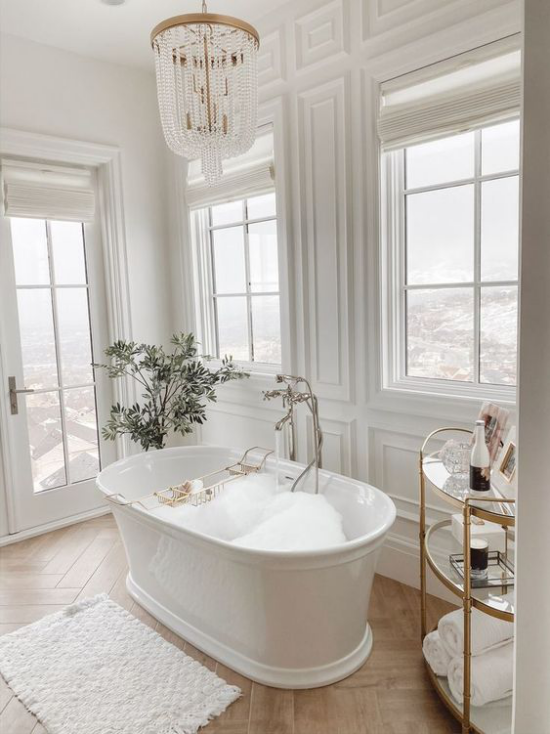 Badezimmer Trends 2021 klassisches Baddesign freistehende Badewanne Holzboden alles andere in Weiß