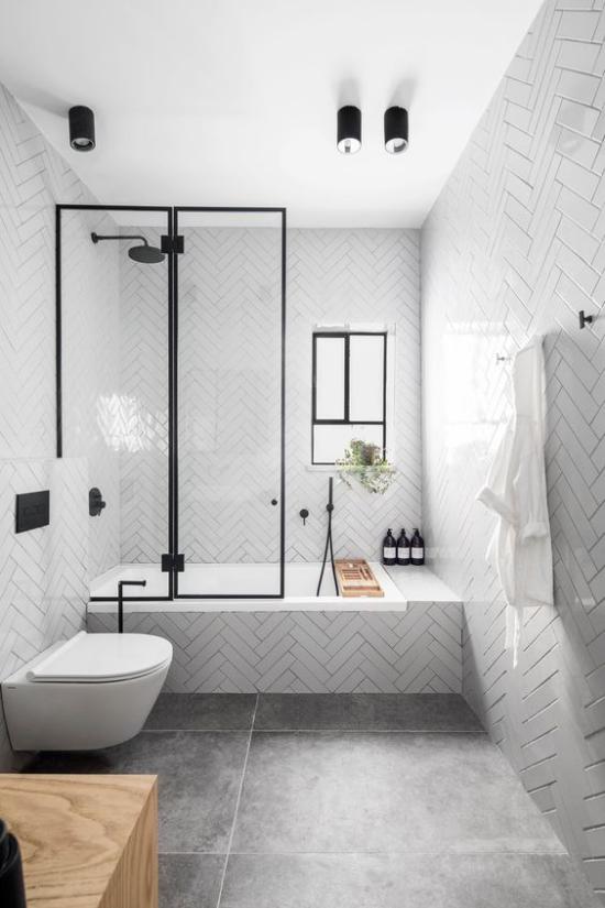 Badezimmer Trends 2021 klassisches Design weiße Fliesen Dusche Glaswände WC schwarze Armaturen graue Bodenfliesen