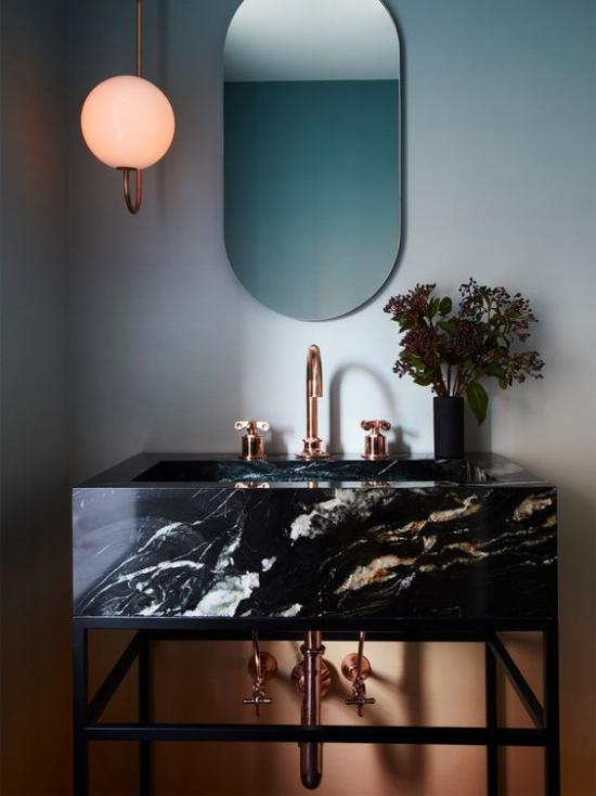 Badezimmer Trends 2021 moderner Waschtisch aus schwarzem Marmor interessante Maserung Badarmatur aus Bronze