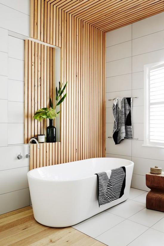 Badezimmer Trends 2021 schickes Baddesign Holzpaneele Holzboden weiße Badewanne weiße Fliesen Tücher