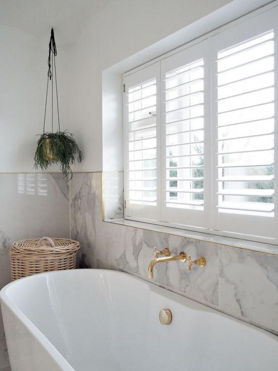 Badezimmer Trends 2021 weiße Badewanne großes Fenster weißer Marmor an der Wand