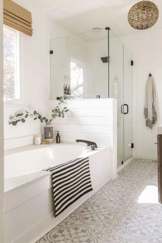 Badezimmer Trends 2021 weiße Badewannen Duschecke daneben Glastür leicht gemusterte Bodenfliesen Badetuch in schwarz-weißen Streifen