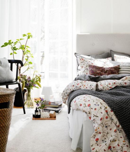 Frühlingsdeko Ideen fürs Schlafzimmer Blumenmuster Bettwäsche weiche Textilien Vase mit Blumen grüne Topfpflanze weicher Teppich