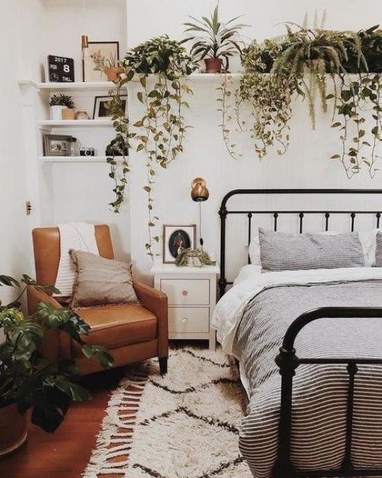 Frühlingsdeko Ideen fürs Schlafzimmer den ganzen Raum begrünen viele grüne Topfpflanzen auf Regal über dem Schlafbett