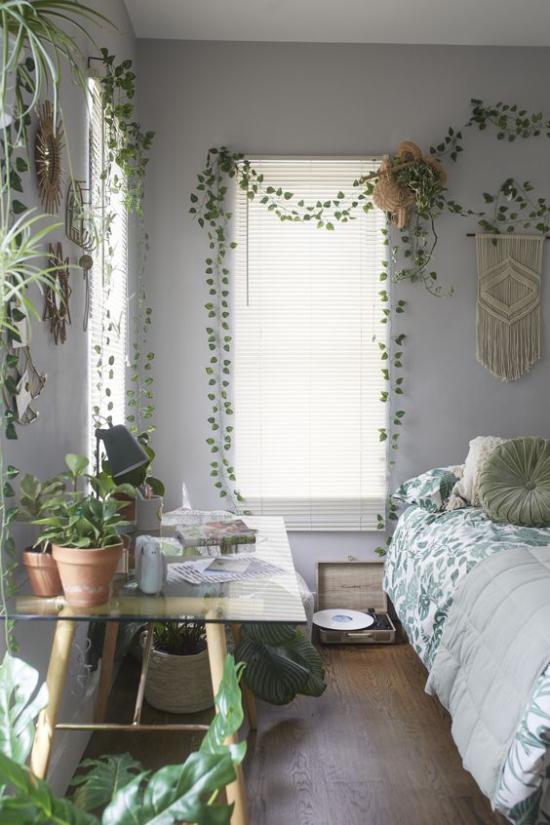 Frühlingsdeko Ideen fürs Schlafzimmer den ganzen Raum begrünen viele grüne Topfpflanzen auf dem Tisch ling grün gemusterte Bettdecke