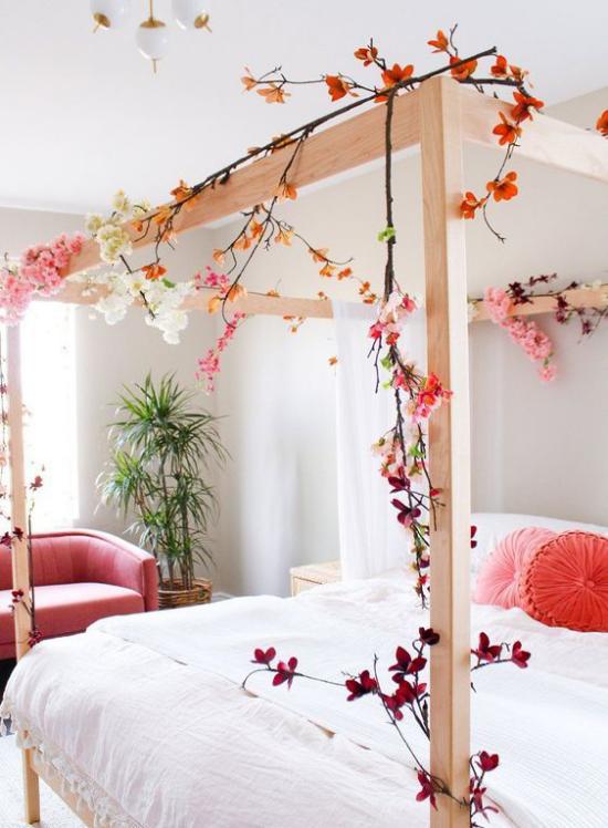 Frühlingsdeko Ideen fürs Schlafzimmer großes Schlafbett Holzrahmen geschmückt blühende Zweige romantische Stimmung