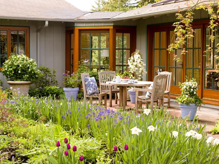 Hinterhof klein aber gemütlich gestaltet Sitzecke Tisch Stühle Polsterkissen Kaffee serviert viele Frühlingsblumen ringsherum