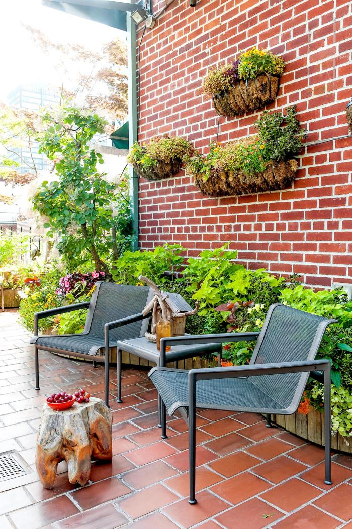 Kleinen Hinterhof einfallsreich gestaltet Sitzecke für zwei Metallstühle Ziegelwand die Zeit im Freien genießen