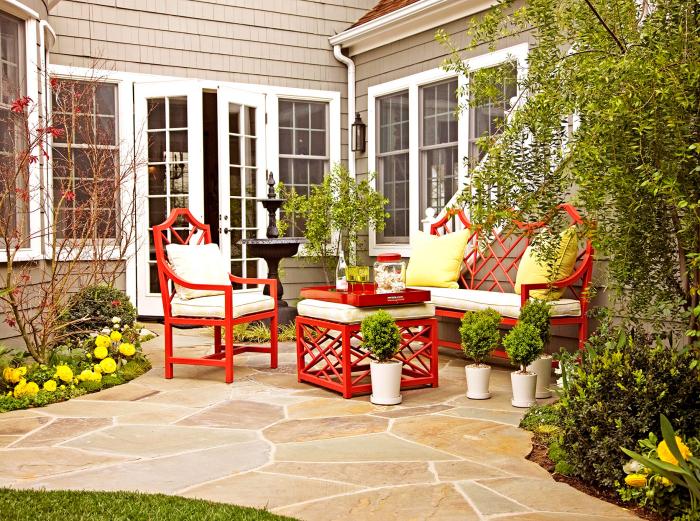 Kleinen Hinterhof gestalten Blumen viel Grün ringsumher bequeme Sitzecke Sessel einladende Sitzecke im Freien
