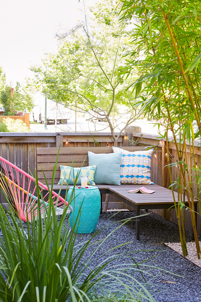 Kleinen Hinterhof gestalten Ecksitzbank am Zaun Deko Kissen Sessel aus Metall hohe grüne Pflanzen