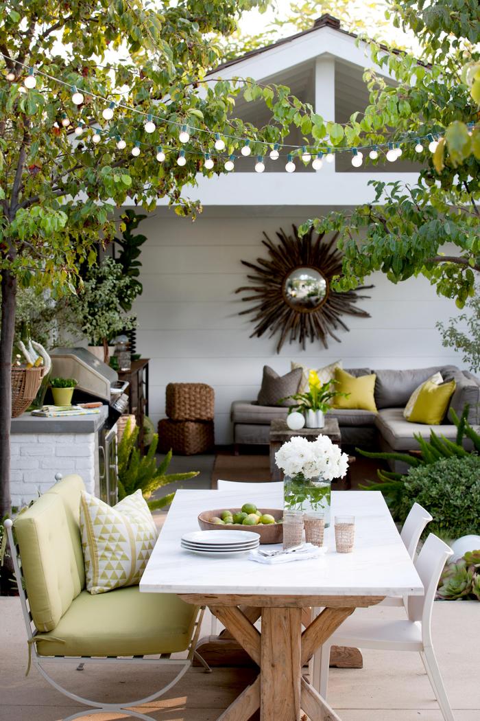 Kleinen Hinterhof gestalten Sitzecke richtige Beleuchtung Lichterkette Outdoor-Küche Essecke