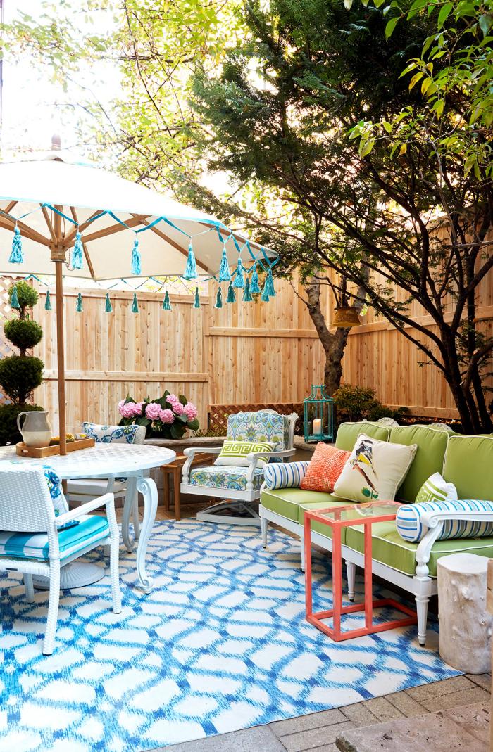 Kleinen Hinterhof gestalten Sitzecke viele Farben Gemütlichkeit Sonnenschirm bequeme Möbel Teppich Blumen hohe Bäume