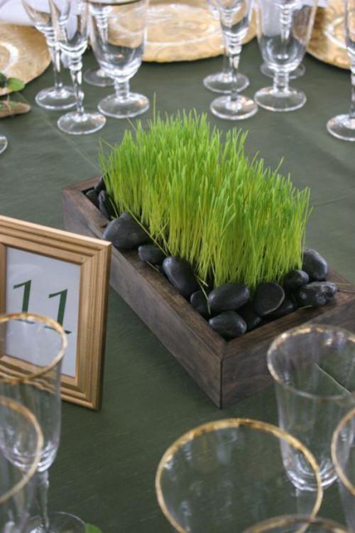 Ostergras selber säen im Holzkasten mit schwarzen Steinen dekoriert auf dem Tisch Blickfang