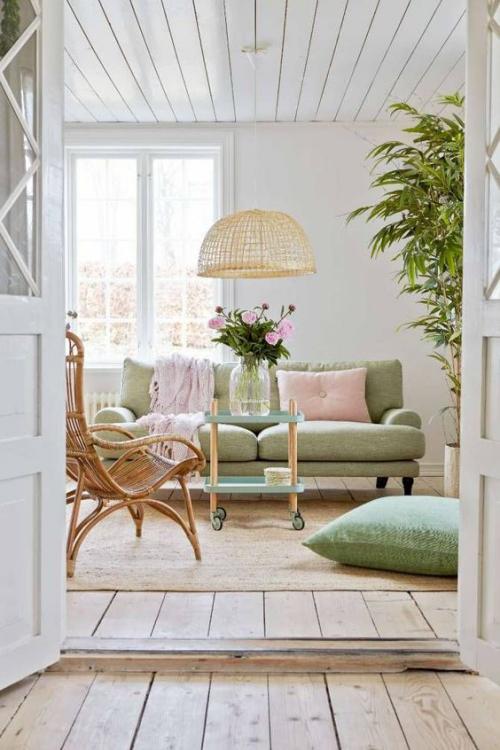 frühlingshafte Dekoideen für das Wohnzimmer Polstermöbel in sanftem Pastellgrün hellrosa Decke Kissen rosafarbene Rosen in Vase auf dem Tisch
