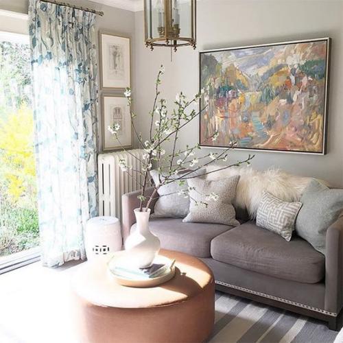 frühlingshafte Dekoideen für das Wohnzimmer blühende Zweige weiße Vase viel Licht Blick zum Innenhof draußen blüht alles geblümte Gardine