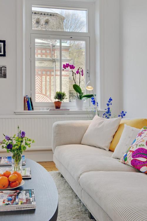 frühlingshafte Dekoideen für das Wohnzimmer helles Sofa schönes Ambiente verschiedene Frühlingsblumen in Vasen und Töpfen Dekokissen