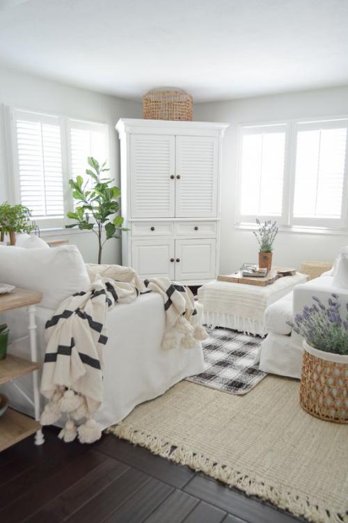 frühlingshafte Dekoideen für das Wohnzimmer im rustikalen Stil gestrickte Wolldecke weiße Hüllen der Möbel grüne Topfpflanzen lavendel im Topf