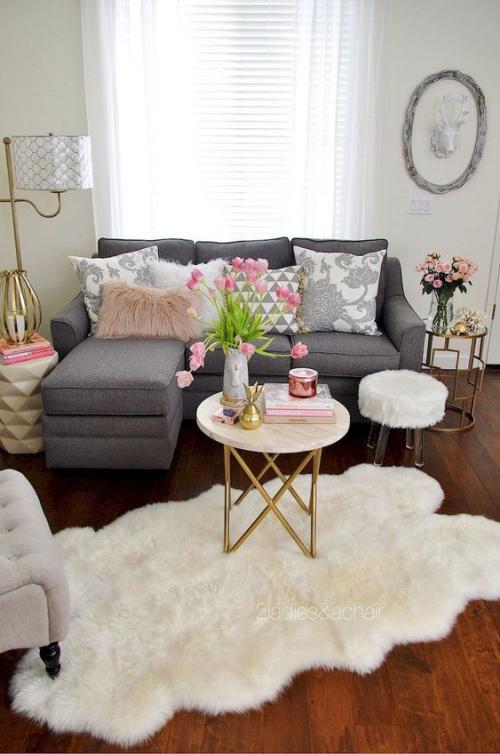 frühlingshafte Dekoideen für das Wohnzimmer sehr gemütliches Ambiente Pelzteppich runder Tisch Tulpen in Vase dunkles Sofa Dekokissen