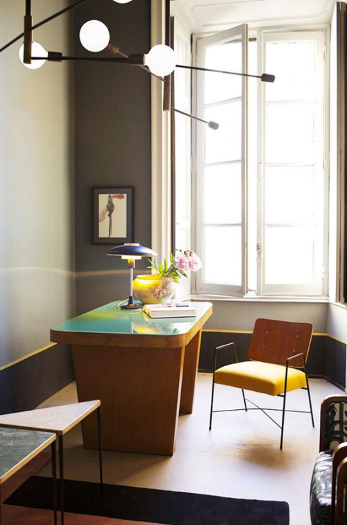 gelbe Akzente im Home Office Büro Inspiration großes Fenster gerundeter Schreibtisch Stuhl Tischlampe runde Vase mit Blumen visuelle Balance
