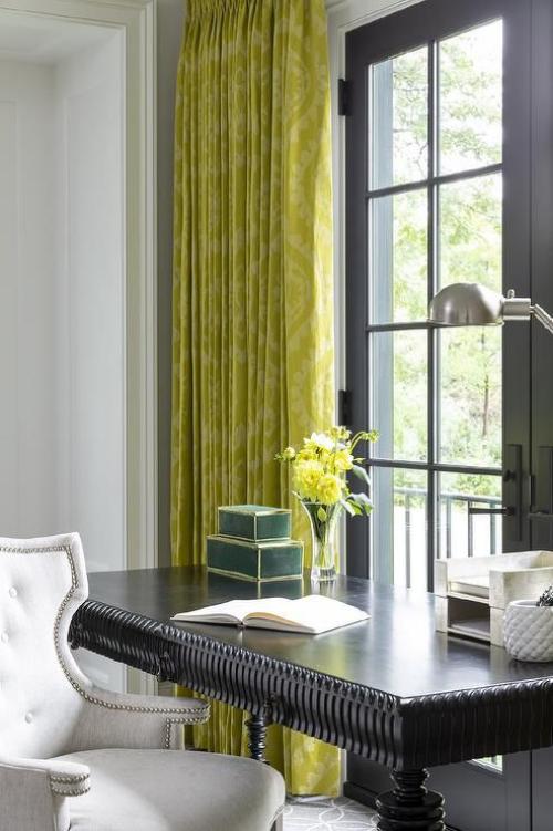 gelbe Akzente im Home Office Büro Inspiration klassischer schwarzer Schreibtisch weißer Sessel gelbgrüne Gardinen Vase mit gelben Blumen