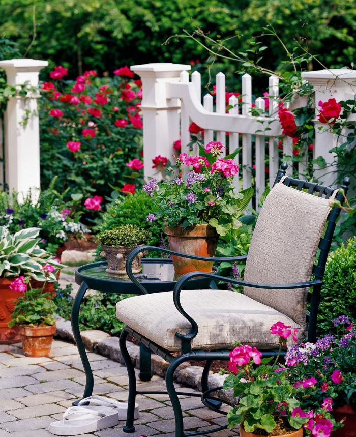 kleinen Garten gestalten Sitzecke halbhoher Zaun viele Gartenpflanzen Topfblumen die Privatsphäre schützen