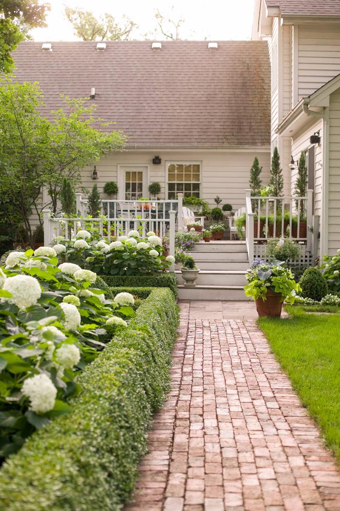 kleinen Garten gestalten Symmetrie weiße Hortensien umrahmen den Pfad zum Haus