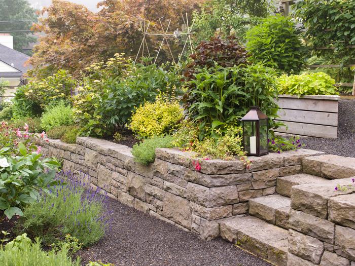 kleinen Garten gestalten gestuftes Gelände Steinstruktur üppige grüne Pflanzen attraktiver Look