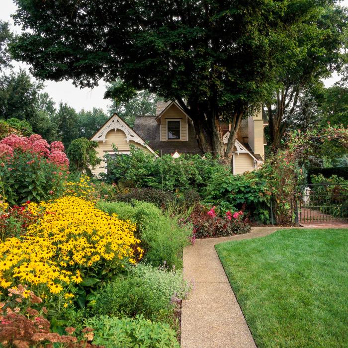 kleinen Garten gestalten schönes Haus viele farbenfrohe Gartenblumen Pfad Zaun grüne Sträucher hoher Baum