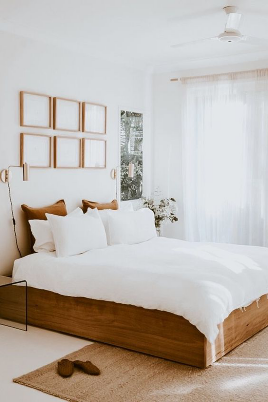kleines Schlafzimmer optisch erweitern Schlafbett aus Holz weiße Bettwäsche Kissen Wanddekoration Fenster viel Licht