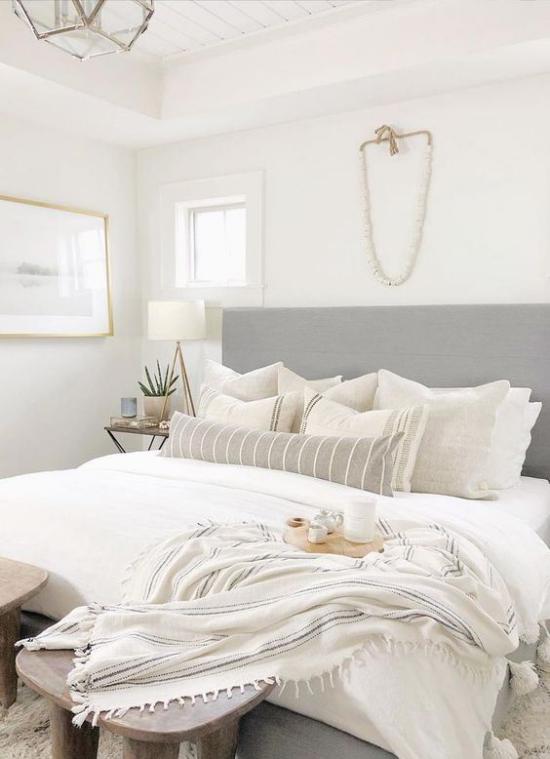 kleines Schlafzimmer optisch erweitern helle Bettwäsche Tagesdecke aus Wolle graues Bettkopfteil viele Deko Kissen