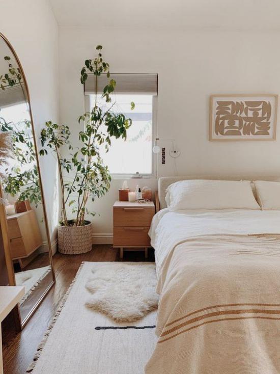 kleines Schlafzimmer optisch erweitern schönes Ambiente helle gedeckte Farben Topfpflanze in der Ecke vor dem Fenster Spiegel links