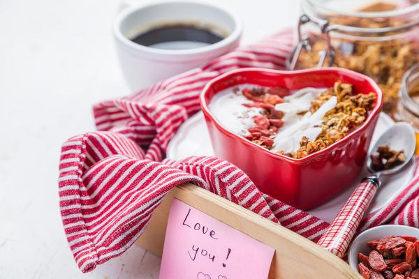 romantisches Frühstück zu zweit Kaffee Müsli mit Joghurt Erdbeeren in Herzform